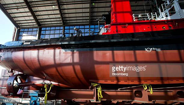 A worker paints the Pacer tugboat as it undergoes repairs at the Seaspan Vancouver Shipyard in North Vancouver British Columbia Canada on Wednesday...