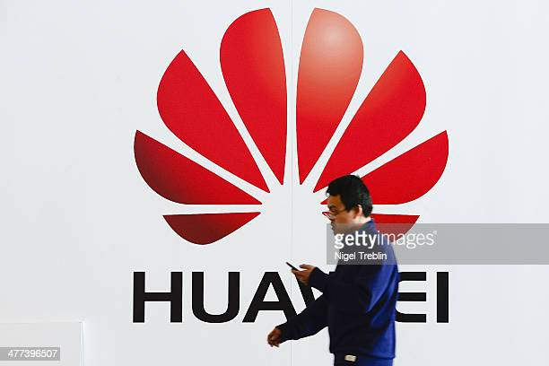 A worker passes an emblem at the Huawei stand at the 2014 CeBIT technology trade fair the day before the fair opens to visitor on March 9 2014 in...