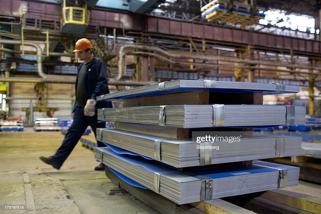 A worker passes batches of steel sheeting during production at OAO Mechel's metallurgical plant in Chelyabinsk, Russia, on Wednesday, July 17, 2013. Mechel, the country's largest producer of coking coal for steelmakers has begun operating its $700m rail production line which can produce 100 meter rails. Photographer: Andrey Rudakov/Bloomberg via Getty Images