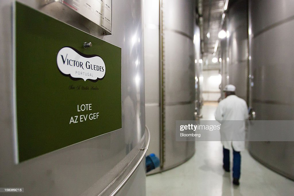 A worker passes between vats of olive oil at the Gallo Worldwide plant in Abrantes, Portugal, on Friday, Dec. 14, 2012. The Iberian nation has already been granted more time to narrow its budget shortfall after tax increases failed to bring in enough money to meet forecasts as the economy heads for a third year of contraction in 2013. Photographer: Mario Proenca/Bloomberg via Getty Images