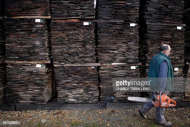 A worker passes by piles of firewood on December 21 2012 in Le PinlaGarenne northwestern France The use of wood for heating cheaper than oil or...