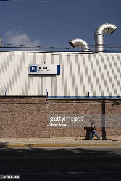 A worker passes in front a General Motors Co assembly plant in Toluca de Lerdo Mexico on Saturday Jan 7 2017 Presidentelect Donald Trump slammed...