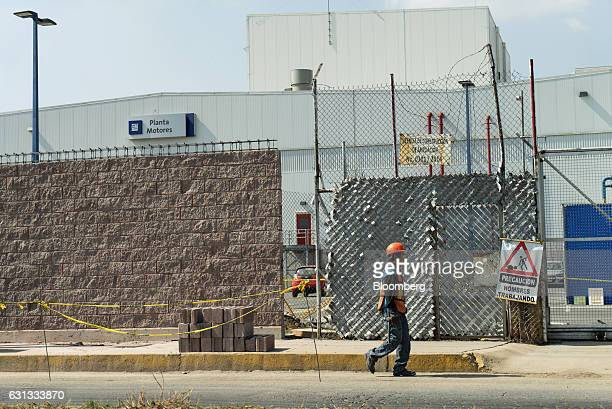 A worker passes in front of a General Motors Co assembly plant in Toluca de Lerdo Mexico on Saturday Jan 7 2017 Presidentelect Donald Trump slammed...