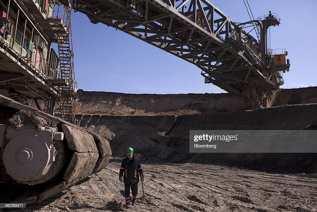 A worker passes in front of a giant excavator as its bucket wheels collect earth during lignite, also known as brown coal, digging operations at the open pit mine operated by PGE Elektrownia Belchatow SA near Belchatow, Poland, on Wednesday, April 2, 2014. Polish power prices are set to stay above German contracts through 2015, reversing a historic discount, as the cost of keeping plants open in the eastern European nation is factored in, according to Vattenfall AB. Photographer: Bartek Sadowski/Bloomberg via Getty Images