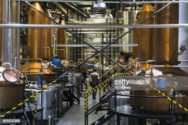 A worker passes in front of copper pot stills at the Patron Spirits Co distillery in Atotonilco El Alto Jalisco Mexico on Tuesday April 4 2017 The...