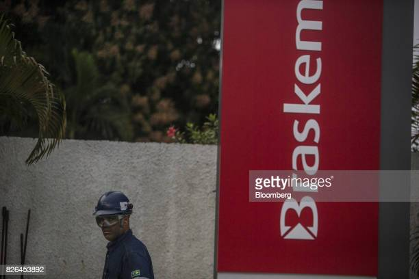 A worker passes in front of signage displayed outside the Braskem SA petrochemical plant in Duque de Caxias Brazil on Friday Aug 4 2017 Petroleo...
