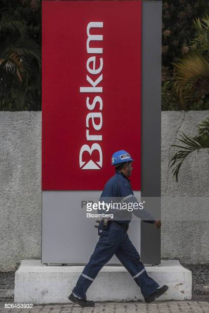 A worker passes in front signage outside the Braskem SA petrochemical plant in Duque de Caxias Brazil on Friday Aug 4 2017 Petroleo Brasileiro SA and...