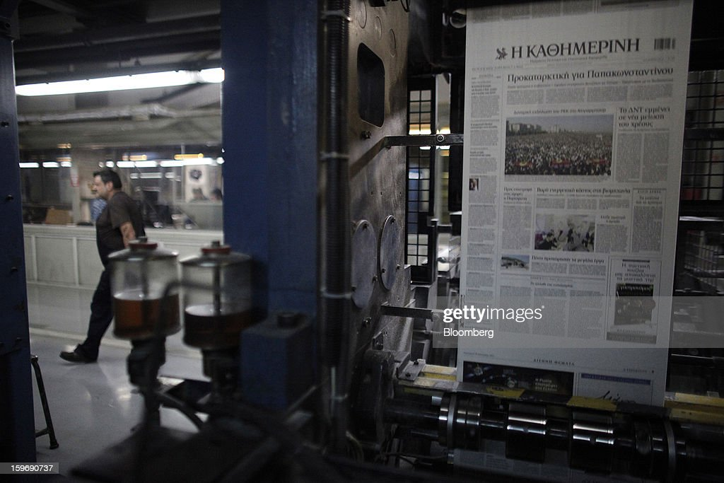 A worker passes Kathimerini newspaper pages as they pass through the automated printing press at the Kathimerini printing plant in Paiania, Greece, on Thursday, Jan. 17, 2013. An anarchist group claimed responsibility for a series of attacks early on Jan. 11 when unidentified perpetrators threw makeshift bombs made from propane gas canisters into the homes of five Greek journalists working for national media saying it was to protest coverage of the country's financial crisis seen as sympathetic to the government. Photographer: Kostas Tsironis/Bloomberg via Getty Images