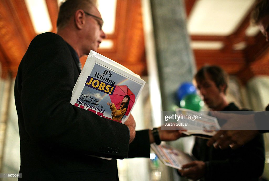 A worker passes out event materials to people waiting to enter the San Francisco Hirevent job fair at the Hotel Whitcomb on March 27, 2012 in San Francisco, California. As the national unemployment rate stands at 8.3 percent, job seekers turned out to meet with recruiters at the San Francisco Hirevent job fair where hundreds of jobs were available.