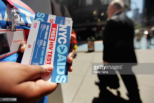 A worker passes out flyers for free HIV testing outside a Walgreens pharmacy in Times Square on June 27 2012 in New York City June 27 is National HIV...