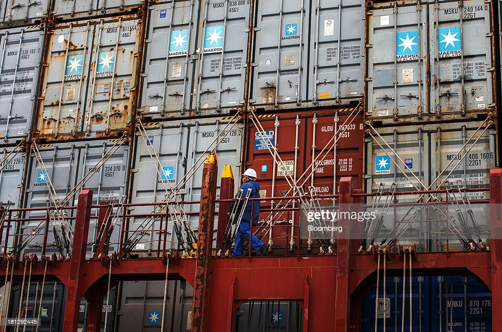 A worker passes shipping containers on board the vessel Maersk Seoul, operated by AP Moeller-Maersk A/S, at the APM Terminal in the Port of Rotterdam, in Rotterdam, Netherlands, on Thursday, Sept. 19, 2013. The pace of economic contraction in the Netherlands, which is in its third recession in five years, is slowing. Photographer: Jasper Juinen/Bloomberg via Getty Images