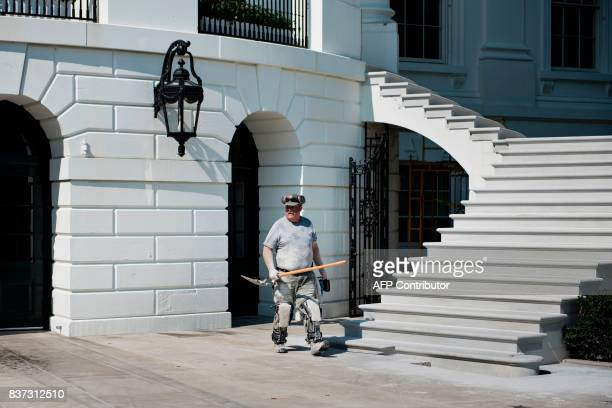 A worker passes stairs on the south portico during summer renovations to the White House on August 22 2017 in Washington DC / AFP PHOTO / Brendan...