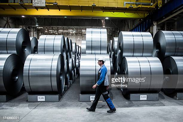 A worker passes stores of high quality steel sheet on the galvanizing line at Voestalpine AG's plant in Linz Austria on Wednesday July 24 2013...