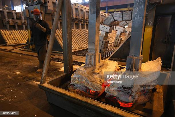 A worker passes used anodes right inside the electrolysis shop at the Irkutsk aluminium smelter operated by United Co Rusal in Shelekhov Russia on...