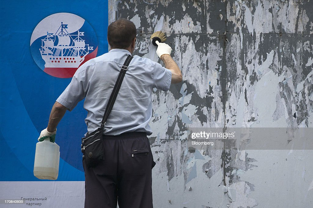 A worker pastes an advertisement for the St. Petersburg International Economic Forum 2013 (SPIEF) outside the main entrance to the Lenexpo center in St. Petersburg, Russia, on Wednesday, June 19, 2013. The Russian Deputy Prime Minister Igor Shuvalov told the conference that the country's World Trade Organization accession negotiations could be further delayed unless several remaining disputed matters are solved. Photographer: Simon Dawson/Bloomberg via Getty Images