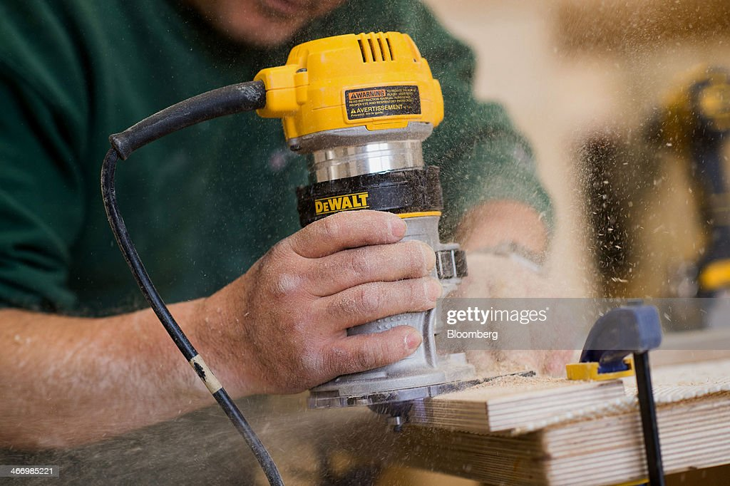 Worker Pedro Rosas Uses A DeWALT Router While Building A Piece Of Furniture  At Casa Kids