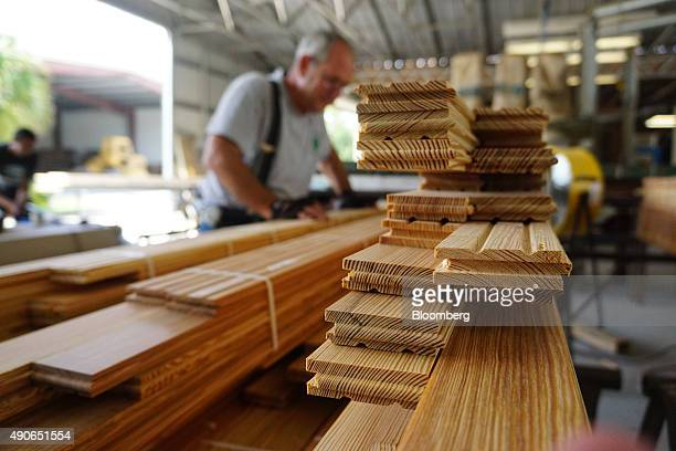 A worker performs a quality check on tongue and groove floor planks before shipment at the Goodwin Co facility in Micanopy Florida US on Wednesday...