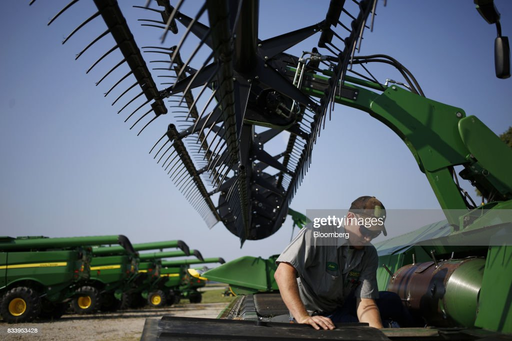 A worker performs maintenance on a Deere & Co. John Deere combine harvester at the Smith Implements Inc. dealership in Greensburg, Indiana, U.S., on Wednesday, Aug. 16, 2017. Deere & Co. is scheduled to release earnings figures on August 18. Photographer: Luke Sharrett/Bloomberg via Getty Images