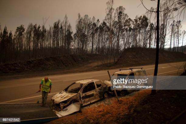 A worker picks up a burnt car from the road after a wildfire took dozens of lives on June 18 2017 near Castanheira de Pera in Leiria district...