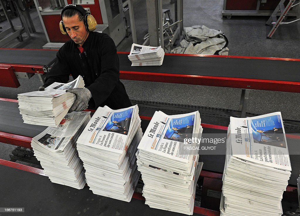 A worker piles up copies of French daily newspaper 'Le Monde' in the printing house of 'Le Midi Libre', the southwestern newspaper on November 20, 2012 in Saint Jean de Vedas. Part of the Le Monde newspaper production is now printed in Saint-Jean-de-Vedas, near the southern city of Montpellier and is now available in the city at midday instead of the following morning.