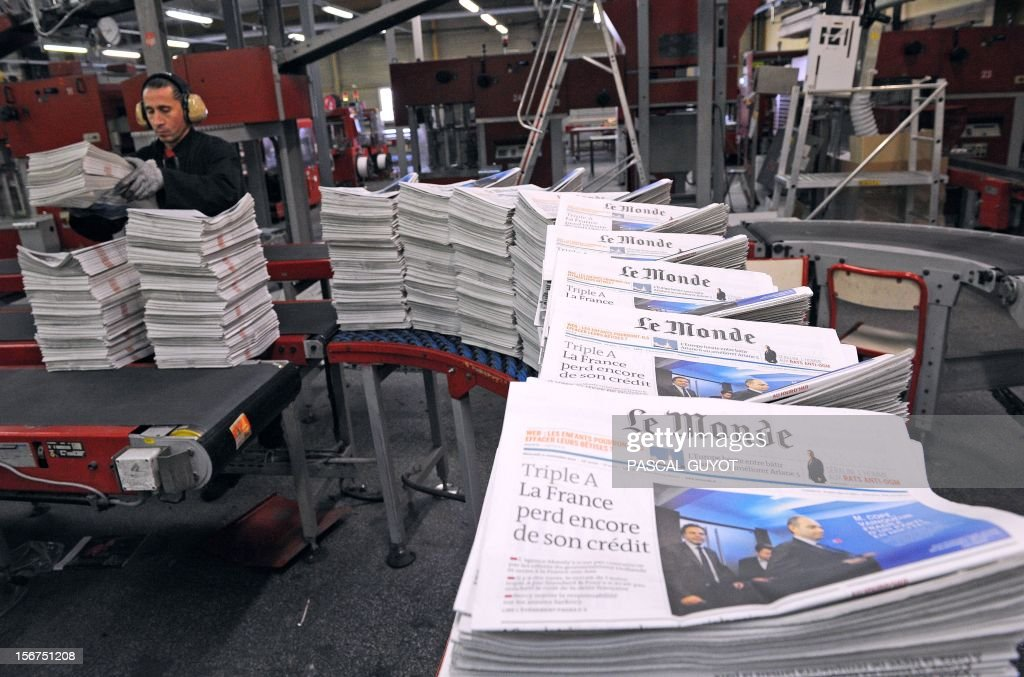 A worker piles up copies of French daily newspaper 'Le Monde' in the printing house of 'Le Midi Libre', the southwestern newspaper on November 20, 2012 in Saint Jean de Vedas. Part of the Le Monde newspaper production is now printed in Saint-Jean-de-Vedas, near the southern city of Montpellier and is now available in the city at midday instead of the following morning. AFP PHOTO / PASCAL GUYOT