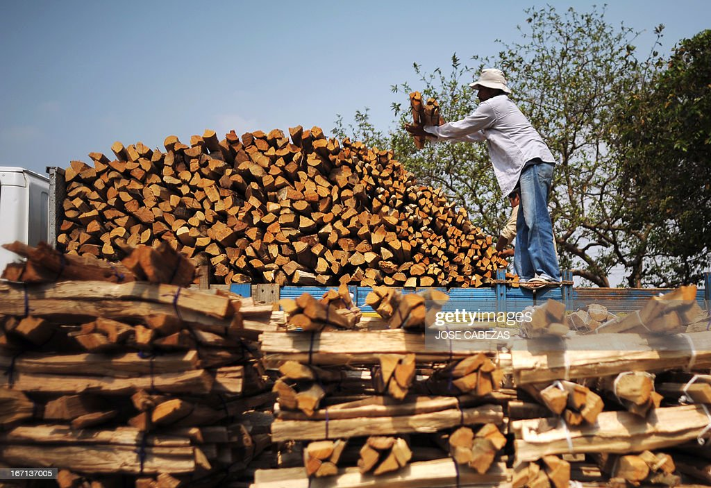 A worker piles up firewood on a truck in Quezaltepeque 25 Km east from San Salvador El Salvador on April 17 2013 Lumberjacks in this region produce...