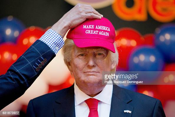 A worker places a cap reading 'Make America great again' on the head of US Presidentelect Donald Trump wax figure during its presentation outside...