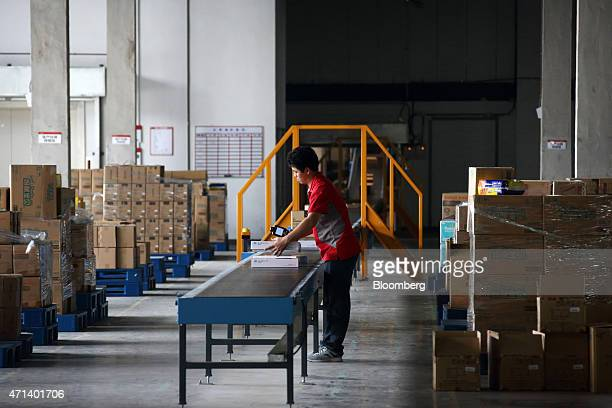 A worker places a package onto a conveyor in the receiving area of a JDcom Inc warehouse in Shanghai China on Monday April 27 2015 JDcom jumped to a...