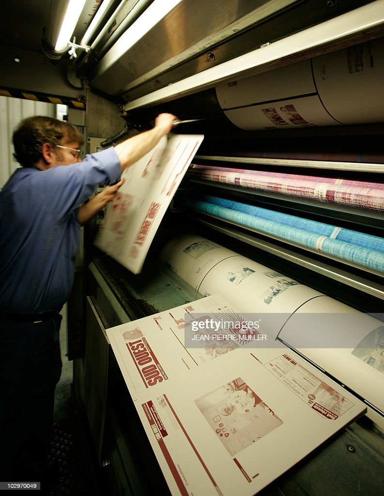 A worker places an aluminium plate in quadrichromy of the front page of a Sud-Ouest edition prior to its use on the rotary printing press machines located in the basement of the newspaper on February 19, 2008 in Bordeaux, southern France.