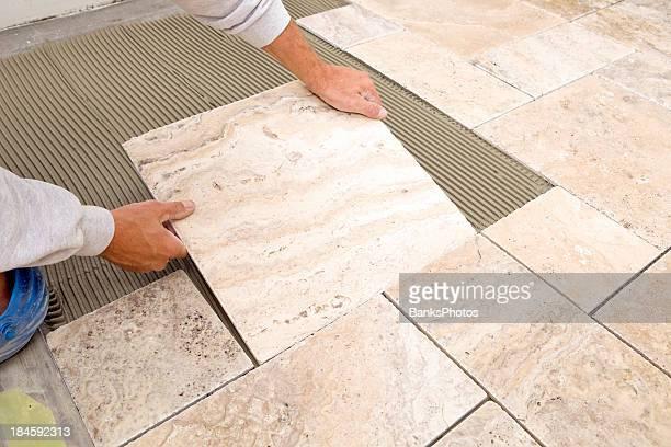 Trabajador lugares nuevos azulejos de mármol en el baño, piso
