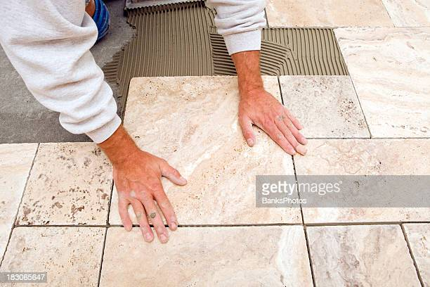 Trabajador lugares nuevos en un baño con azulejos de piso