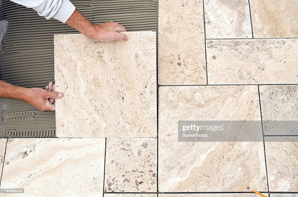 Floor Tile Workers : Worker places new tile on a bathroom floor stock photo