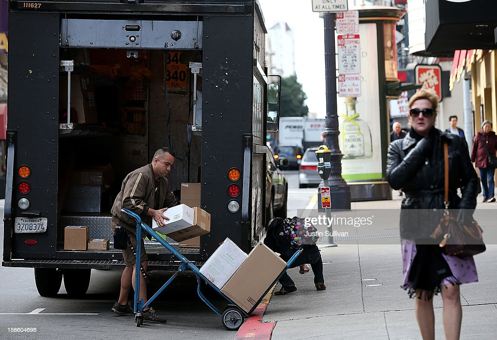 A UPS worker places packages on a hand cart on December 20, 2012 in San Francisco, California. With less than one week to go before Christmas, today is expected to be the busiest day in the history of UPS and they are expecting to ship an estimated 28 million packages around the globe.
