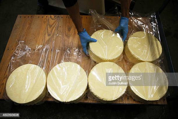 A worker places wheels of cheese on a wooden racks in a cooler at Vella Cheese on June 10 2014 in Sonoma California The Food and Drug Administration...