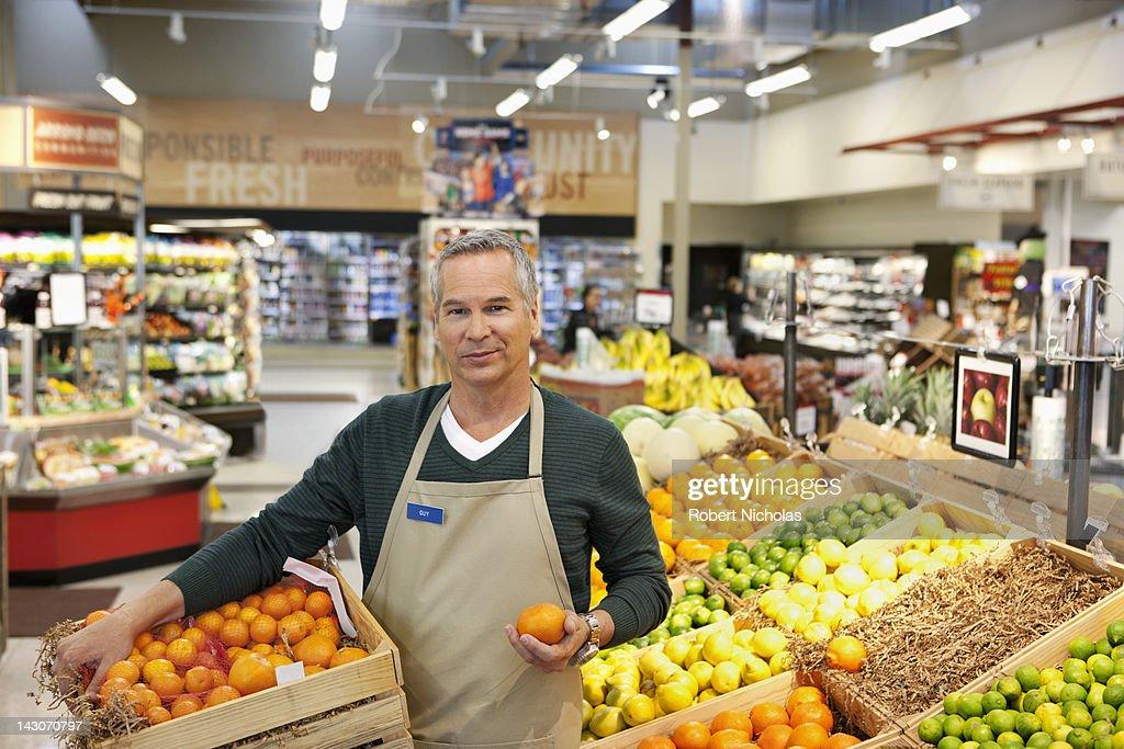 Worker placing oranges in supermarket display : Stock Photo