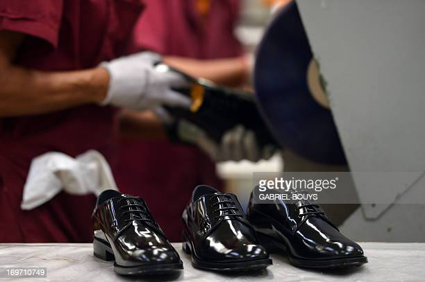 A worker polishes a shoe in the factory of the Italian shoes and luxury leather goods Tod's on May 28 2013 at the headquarters of the company in...