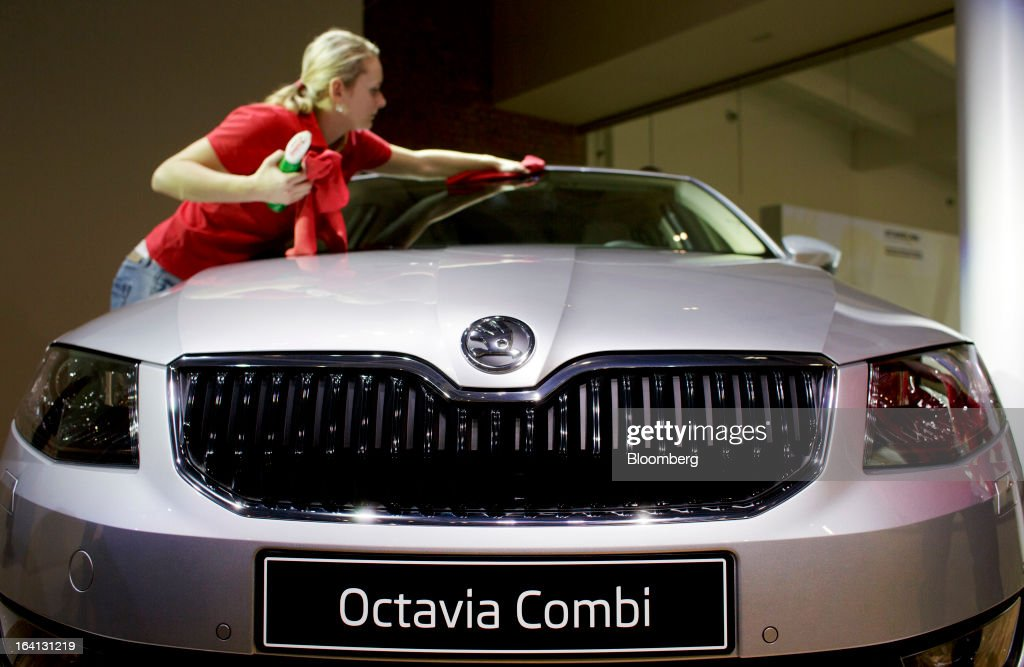 A worker polishes a Skoda Octavia Combi automobile, produced by Skoda Auto AS, the Czech unit of Volkswagen AG, on display during the company's results news conference in Mlada Boleslav, Czech Republic, on Wednesday, March 20, 2013. Volkswagen AG's Czech brand Skoda said it's 'fundamentally' confident that 2013 deliveries will rise as the introduction of a new Octavia small car version and Spaceback hatchback more than offsets a drop in European demand. Photographer: Martin Divisek/Bloomberg via Getty Images