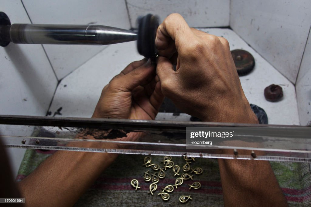A worker polishes jewelry pieces on a lapping machine at the Kama Schachter Jewelry Pvt Ltd. diamond studded gold and platinum manufacturing facility in Mumbai, India, on Wednesday, June 19, 2013. India's exports of diamonds and gold jewelry grew 5.2% to $6.1 billion in April and May, says the Gem & Jewellery Export Promotion Council on June 18, 2013. Photographer: Adeel Halim/Bloomberg via Getty Images