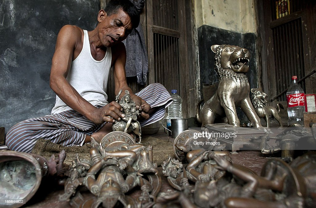 A worker polishes sculptures at Dhamrai Metal Crafts on October 5, 2013 in Dhaka, Bangladesh. The owner of the metal crafts shop, Sukanta Banik, creates bronze sculptures in the art of 'lost wax casting.' The business has been in his family for 200 years. The pieces are first molded in wax, then encased in clay, then baked in the oven, after which metal is poured into the mold. One piece can take up to 10 months to make. The business is suffering because most of these items he creates can now be mass produced in plastic, and as a Hindu artist working in Islamic Bangladesh, the 'depiction of all humans and animals are discouraged by the majority religion.' Recently it took a year and a half to send an order overseas, when Bangladeshi customs held his work in hopes for a bribe.