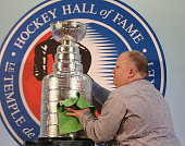 A worker polishes up the Stanley Cup prior to a media opportunity with the 2014 Hall of Fame inductees at the Hockey Hall of Fame on November 14 2014...
