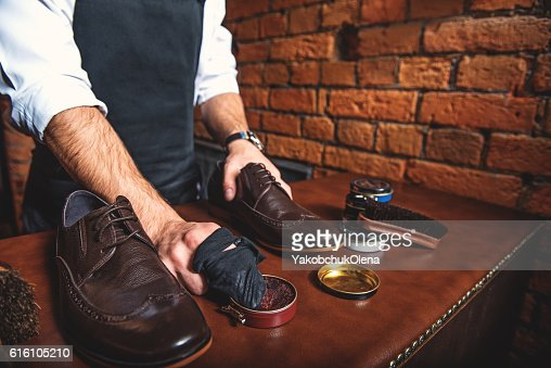 worker polishing a pair of shoes : Stock Photo