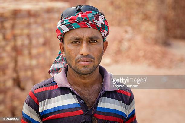 A worker poses for a photo in front of bricks on April 12 2016 in Mongla Bangladesh