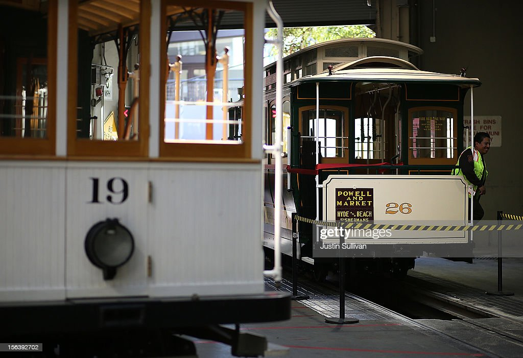 A worker poses for a photo on San Francisco Cable Car #26 during a service inauguration ceremony for the newly restored vintage Cable Car on November 14, 2012 in San Francisco, California. A service inauguration ceremony kicked off a new life for San Francisco Cable Car #26 that was originally built in 1890 and has been fully restored by hand and put back in service on the streets of San Francisco.