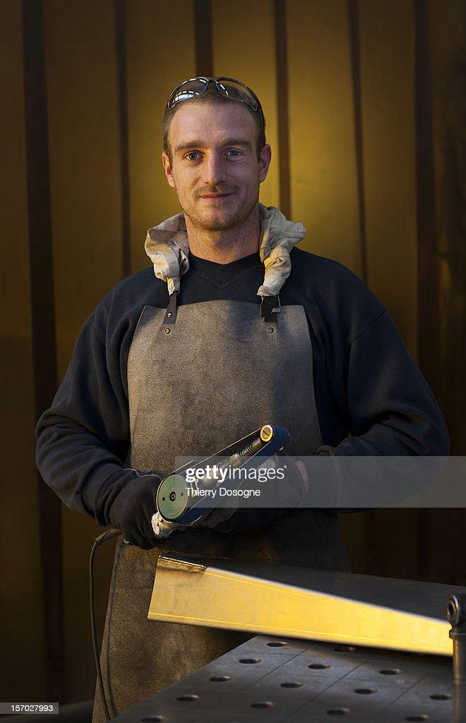 Worker posing in metal worshop : Stock Photo