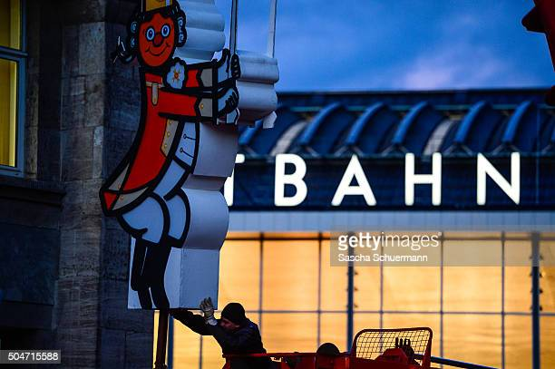 A worker positions a carnival decoration in front of Hauptbahnhof main railway station stands near Hauptbahnhof main railway station where on New...