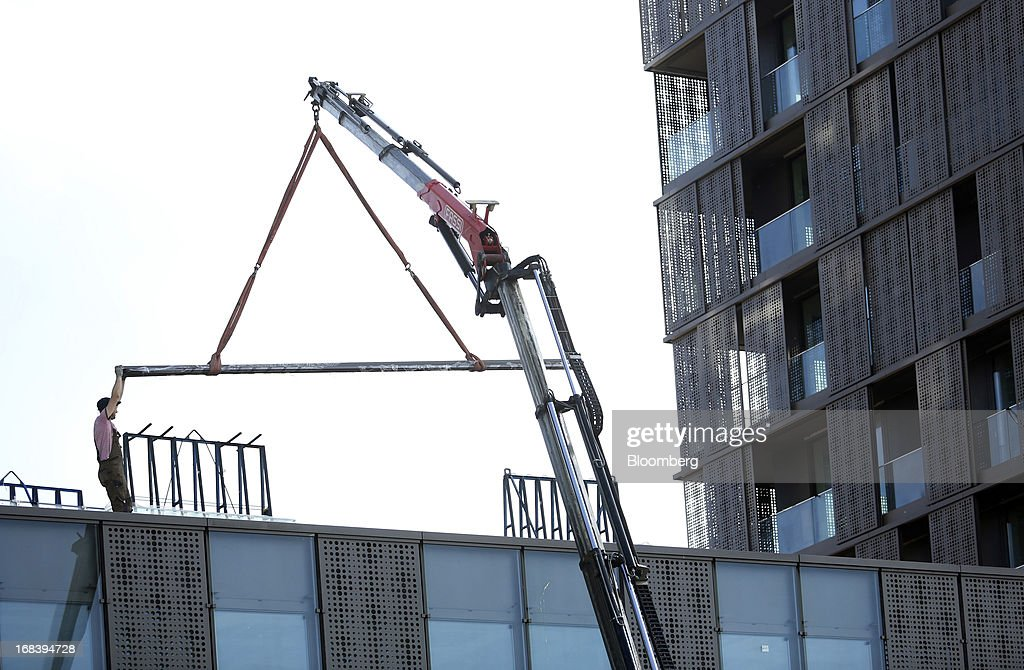A worker positions a steel beam hanging from a crane at a construction site for new residential apartments in Ljubljana, Slovenia, on Wednesday, May 8, 2013. Slovenia's recession will stretch into next year on weak domestic demand as the euro-area country teeters on the brink of needing an international bailout, the European Commission said. Photographer: Chris Ratcliffe/Bloomberg via Getty Images