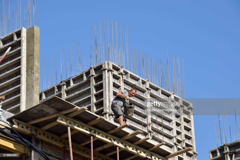 Worker pouring cement. Construction of a multistory building : Stock Photo