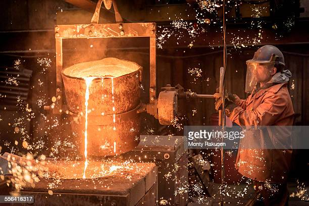 Worker pouring molten metal in foundry