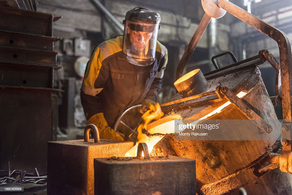 Worker pouring molten steel into moulds in foundry
