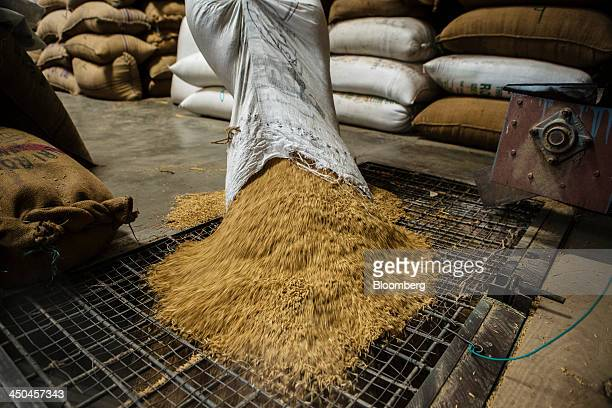 A worker pours a bag of rice grain into a dehusking machine at the KRK Modern Rice Mill in Kothapeta Tamil Nadu India on Thursday Nov 14 2013 Record...